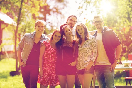 leisure, holidays, reunion, people and friendship concept - happy teenage friends hugging at summer garden party Stock Photo