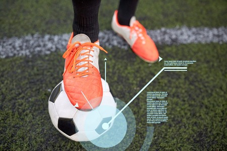 sport, football and technology - soccer player playing with ball on field Stock Photo