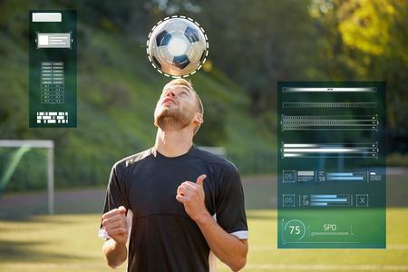 sport, voetbal en mensen - voetballer spelen en jongleren bal met behulp van header techniek op veld Stockfoto
