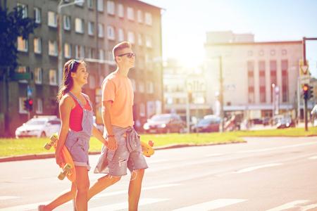 zomervakantie, extreme sport en de mensen concept - happy teenage paar met korte moderne cruiser skateboards kruising stad crosswalk