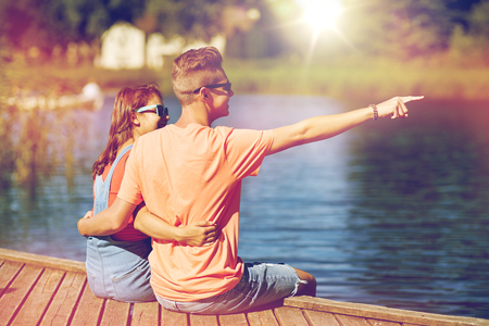 holidays, vacation, love and people concept - happy smiling teenage couple hugging and pointing finger to something on river berth at summer Imagens - 82198345