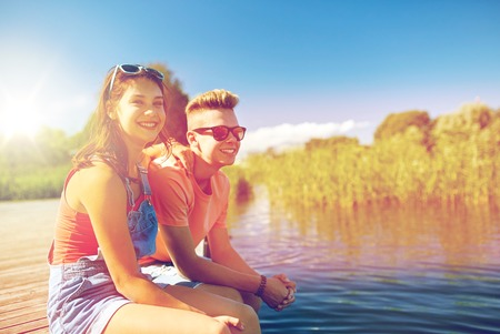 holidays, vacation, love and people concept - happy teenage couple sitting on river berth at summer