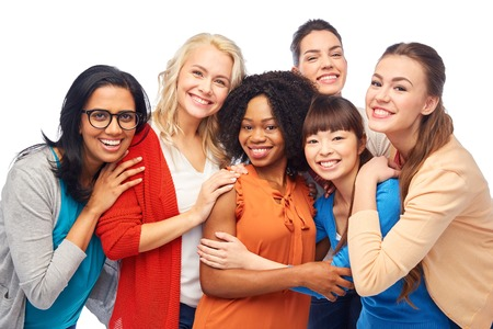 diversity, race, ethnicity and people concept - international group of happy smiling different women over white hugging Foto de archivo