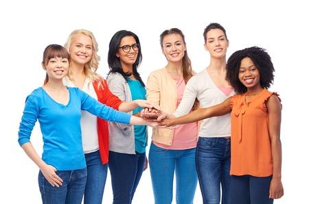Concepto de diversidad, raza, etnicidad y personas - grupo internacional de sonrientes felices diferentes mujeres sobre blanco tomados de la mano juntos Foto de archivo - 82198359