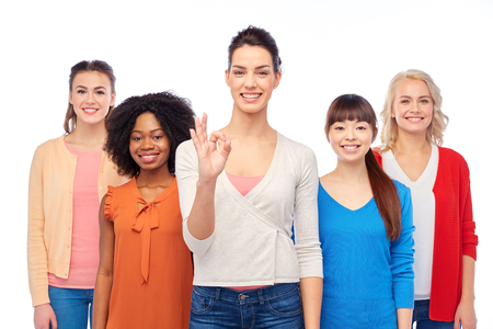 diversity, race, ethnicity and people concept - international group of happy smiling different women over white showing ok hand sign Stock Photo