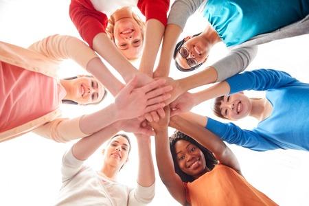 diversiteit, ras, etniciteit en mensenconcept - internationale groep gelukkige glimlachende verschillende vrouwen over witte holdingshanden samen Stockfoto