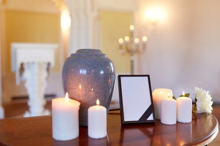 begrafenis en rouw concept - fotolijst met zwart lint, crematie urn en brandende kaarsen op tafel in de kerk Stockfoto