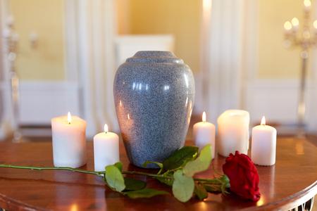 begrafenis en rouw concept - rode roos en crematie urn met brandende kaarsen op tafel in de kerk