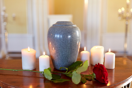 funeral and mourning concept - red rose and cremation urn with burning candles on table in church Stock Photo