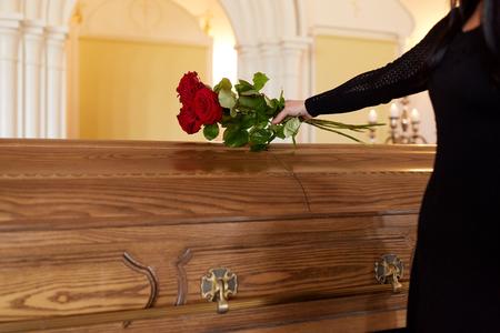 Concetto di lutto e persone - donna con rose rosse e bara al funerale in chiesa Archivio Fotografico - 82198389