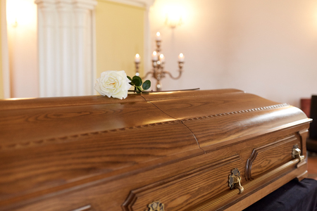 funeral and mourning concept - white rose flower on wooden coffin at funeral in church Stock Photo