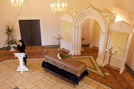 La gente e il concetto di lutto - piangere donna vicino bara al funerale nella chiesa cristiana ortodossa Archivio Fotografico - 82198393
