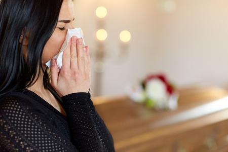 mensen en rouwconcept - sluit omhoog van schreeuwende vrouw met doodskist bij begrafenis in kerk