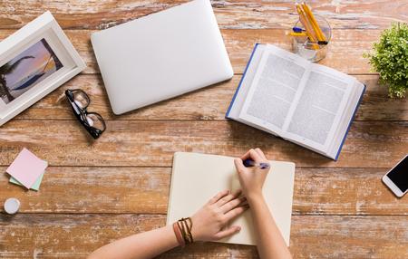 zaken, onderwijs en mensenconcept - handen met boek die aan notitieboekje bij houten lijst schrijven Stockfoto
