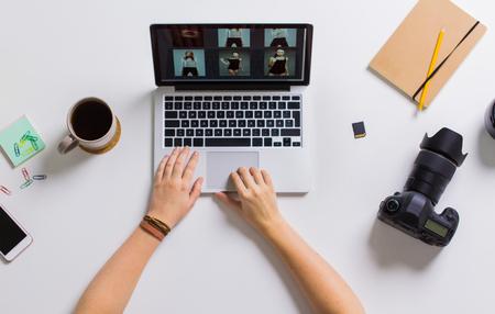 Vrouw handen met camera werken op de laptop aan tafel Stockfoto