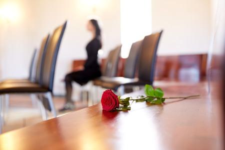 Rode rozen en vrouw die bij de begrafenis in de kerk huilen