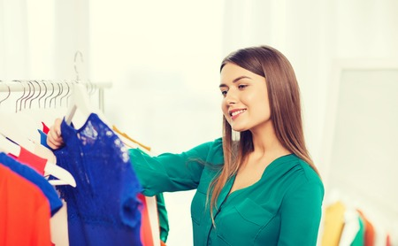 clothing store: clothing, fashion, style and people concept - happy woman choosing clothes at home wardrobe
