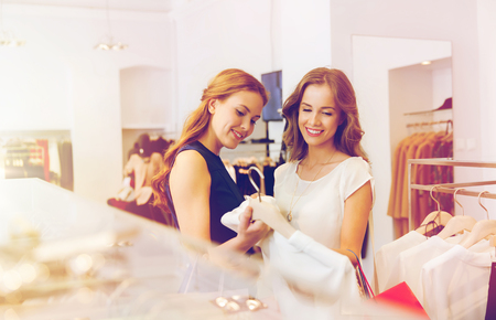 clothing store: happy women with shopping bags at clothing shop