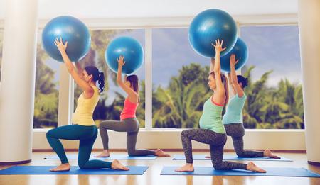 Gelukkige zwangere vrouwen die met de bal in de sportschool uitoefenen Stockfoto