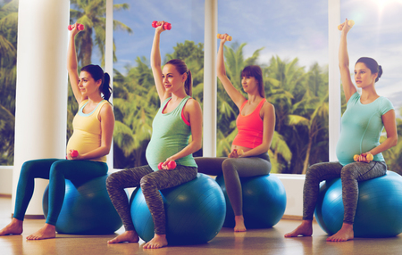 happy pregnant women exercising on fitball in gym photo
