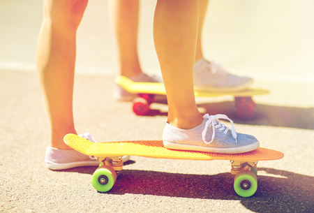 close up of female feet riding short skateboard
