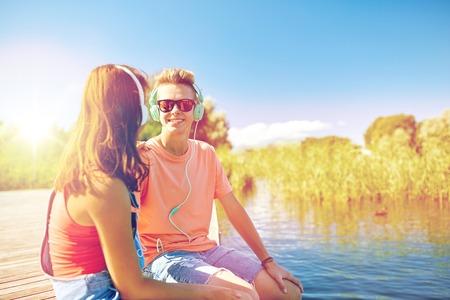 happy teenage couple with earphones on river berth Imagens
