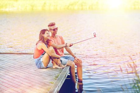happy teenage couple taking selfie on smartphone
