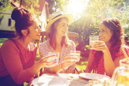 Mujeres felices con bebidas en la fiesta de jardín de verano
