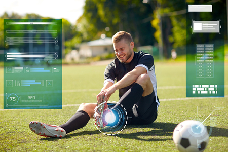 specification: injured soccer player with ball on football field Stock Photo