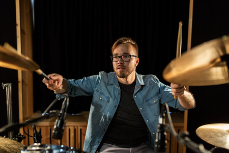 male musician playing drums and cymbals at concert photo