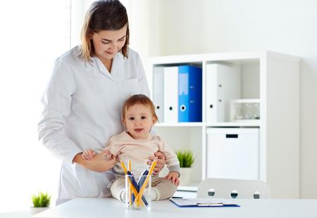 행복 한 의사 또는 소아과 클리닉에서 아기와 함께