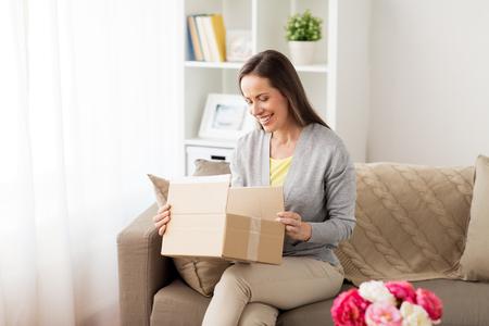 Lächelnde Frau, die Pappschachtel öffnet Standard-Bild - 82483222