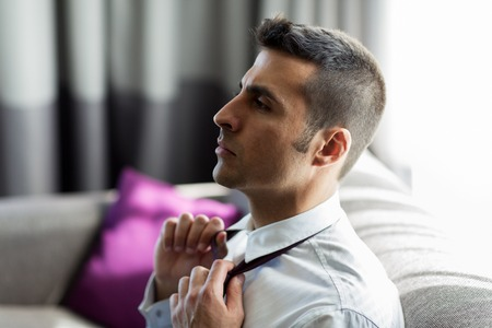 businessman taking off his tie at hotel room