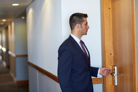 businessman with keycard at hotel or office door Stock Photo