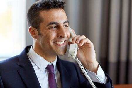 businessman calling on phone at hotel or office