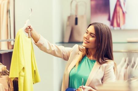 gelukkige jonge vrouw kleding in winkelcentrum te kiezen Stockfoto