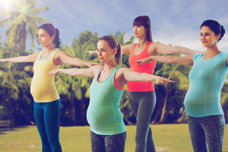 happy pregnant women exercising in gym photo
