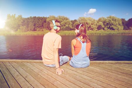 teenage couple with headphones on river berth