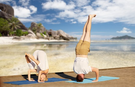 couple making yoga over tropical beach background Stock Photo - 82489085