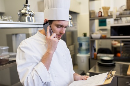chef calling on smartphone at restaurant kitchen