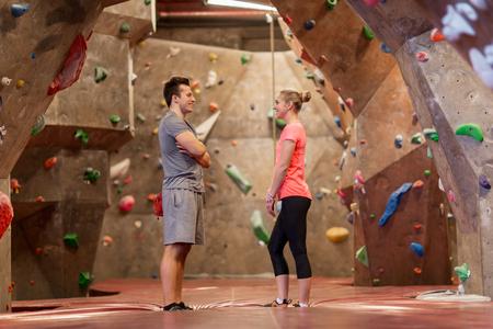 man and woman talking at indoor climbing gym