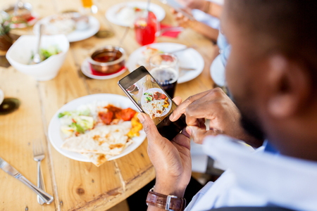 body parts cell phone: hands with smartphone picturing food at restaurant