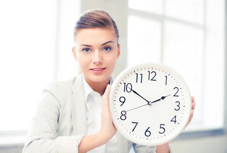 aantrekkelijke onderneemster die witte klok toont Stockfoto
