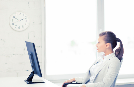 career timing: businesswoman looking at wall clock in office
