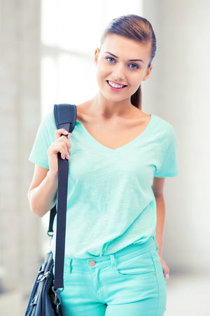 carrying: happy smiling student girl with school bag Stock Photo