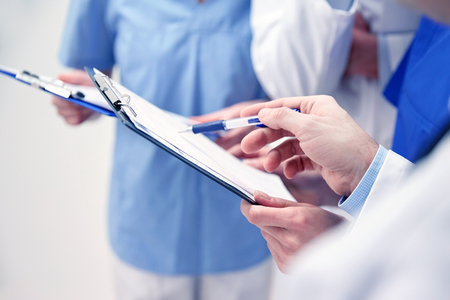 close up of doctors with clipboard at hospital Stockfoto