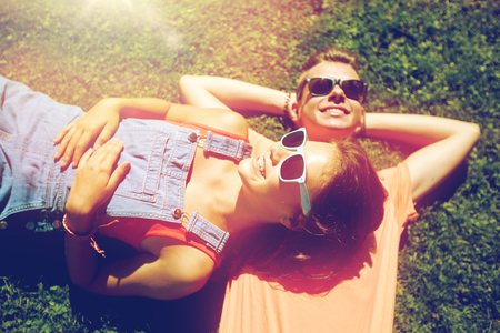 happy teenage couple lying on grass at summer photo