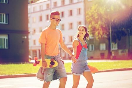 paso de peatones: pareja de adolescentes con monopatines en calle de la ciudad