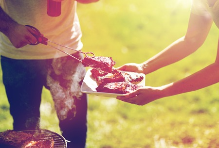 man cooking meat at summer party barbecue