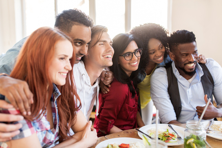 Glückliche Freunde im Restaurant essen Standard-Bild - 82547480